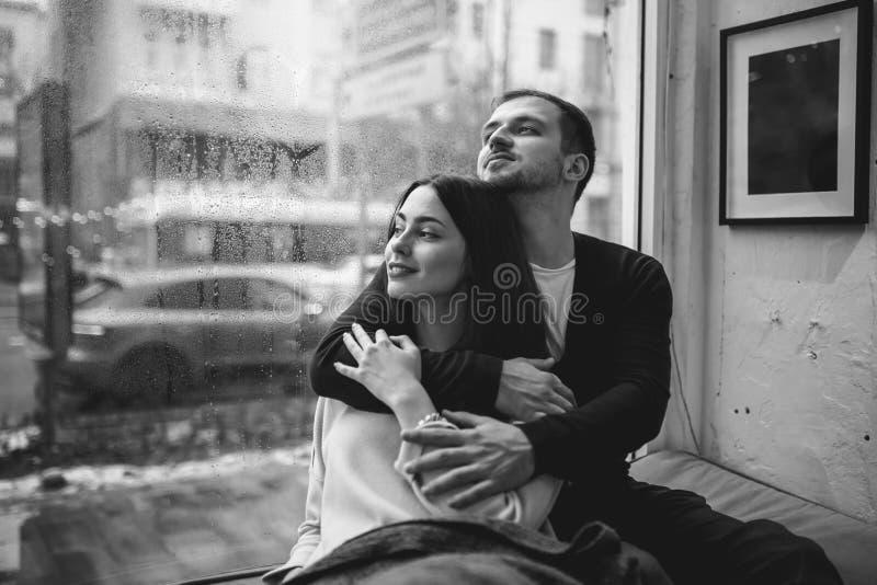 Pares rom?nticos El individuo de amor abraza a su novia hermosa que se sienta en el alf?izar en un caf? acogedor imagen de archivo libre de regalías