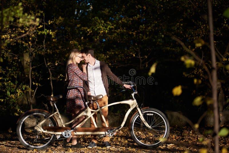 Pares rom?nticos, homem e fim atrativo da menina junto na bicicleta em tandem no parque escuro do outono imagens de stock