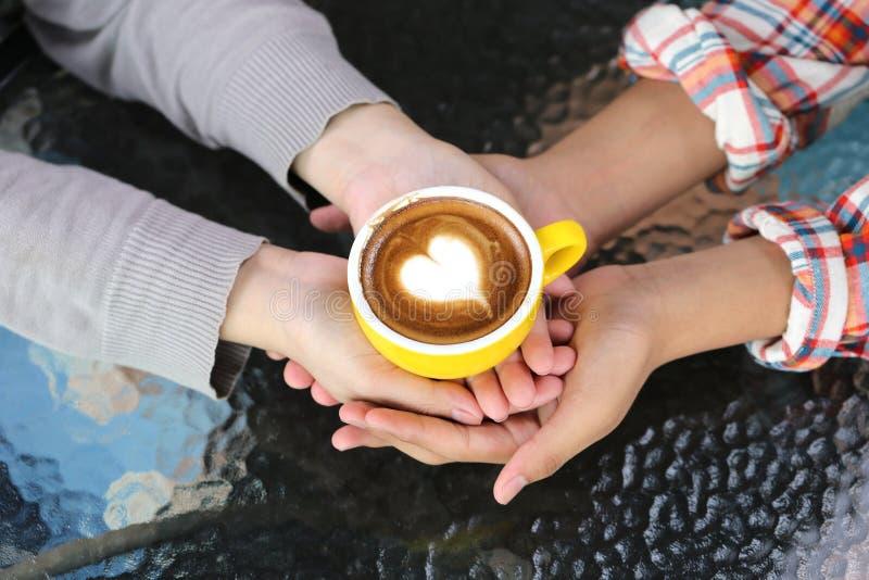 Pares rom?nticos na m?o do amor que guarda dois copos da arte do latte com teste padr?o o cora??o na tabela na cafetaria foto de stock