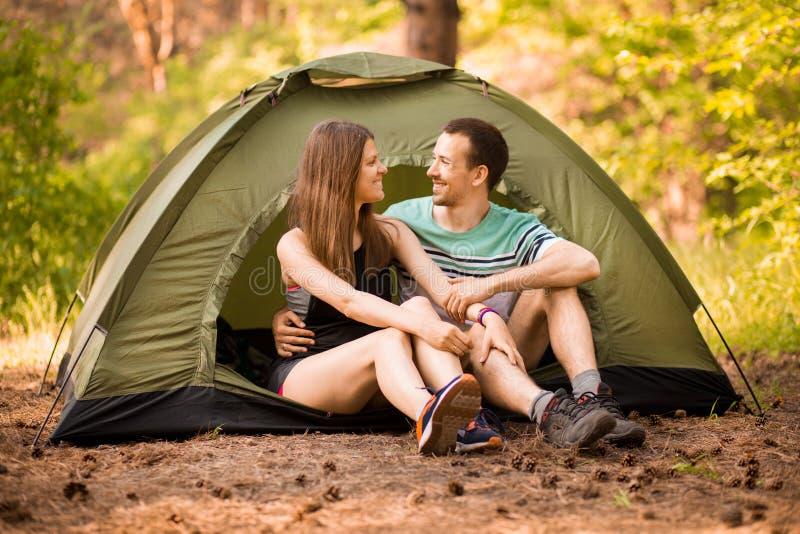 Pares rom?nticos que acampam fora e que sentam-se na barraca Homem e mulher felizes em férias românticas fotografia de stock