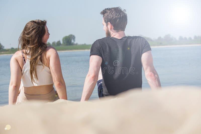 Pares rom?nticos que se sientan en la playa y que disfrutan de la opini?n hermosa del mar Concepto del amor y de las tarjetas del fotos de archivo