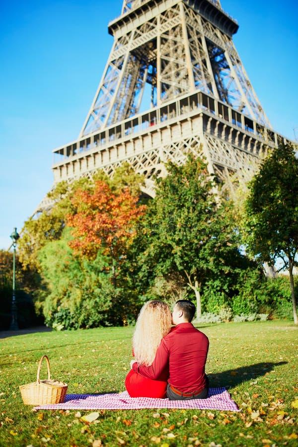 Pares rom?nticos que tienen comida campestre en la hierba cerca de la torre Eiffel imágenes de archivo libres de regalías