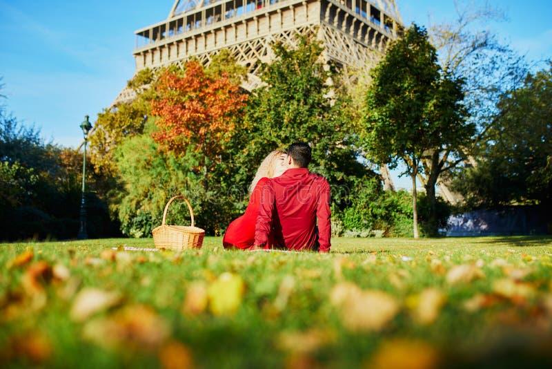 Pares rom?nticos que tienen comida campestre en la hierba cerca de la torre Eiffel fotografía de archivo