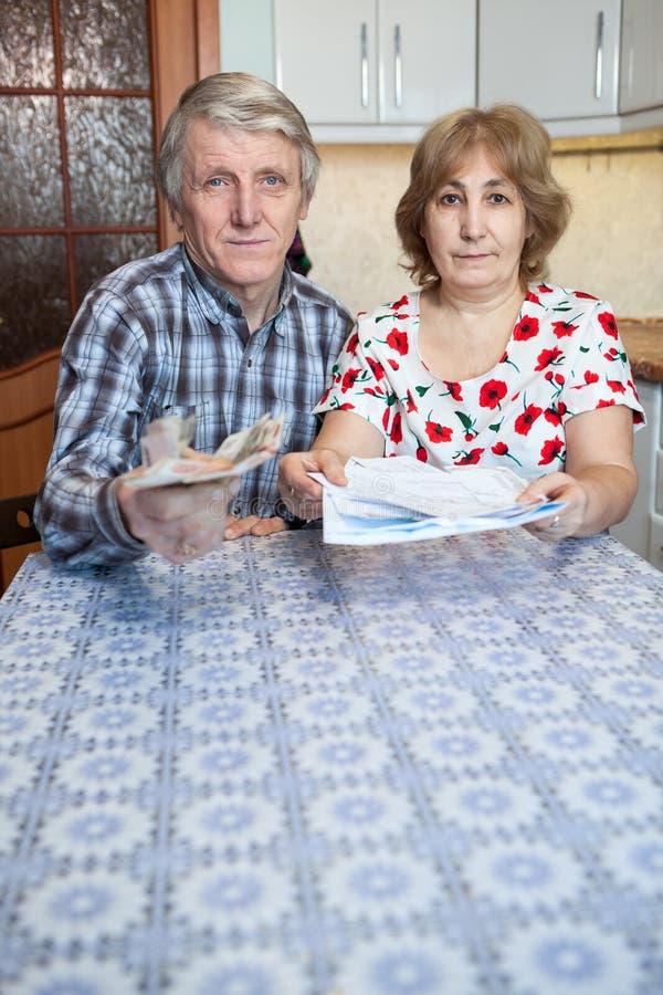 Pares rusos del retiro que estiran cuentas y el dinero del efectivo en las manos, sentándose en la tabla de cocina, copyspace fotos de archivo