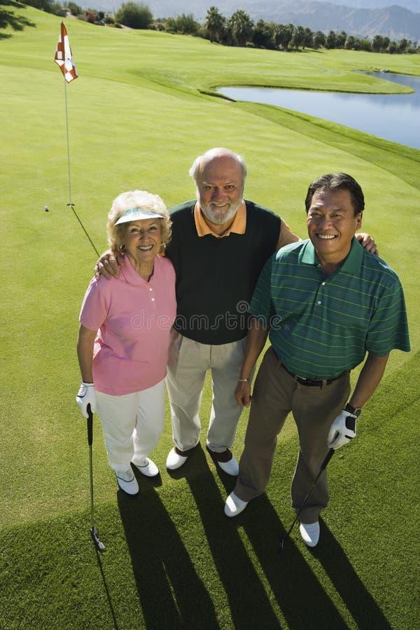 Pares sênior com o instrutor no campo de golfe fotos de stock royalty free