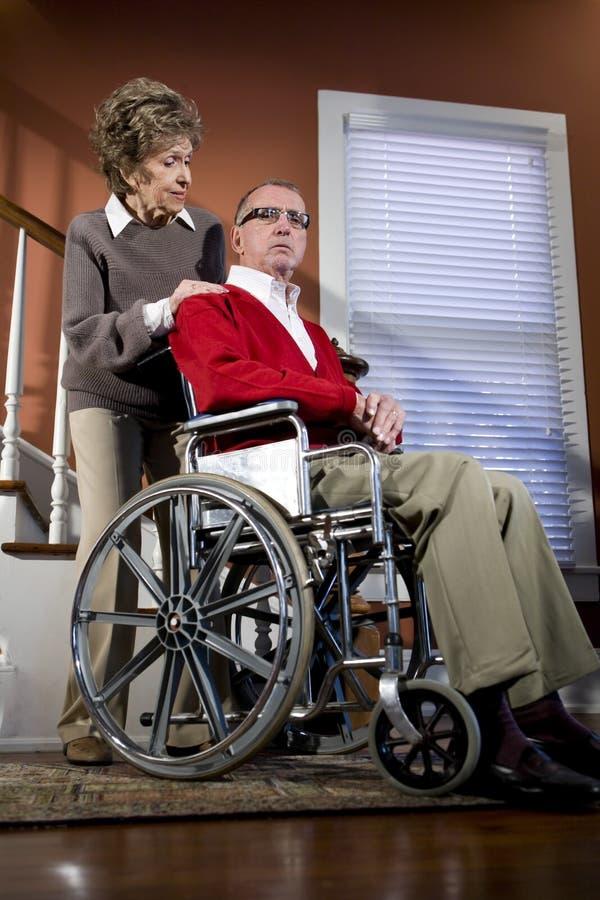 Pares sênior em casa, homem na cadeira de rodas imagens de stock royalty free