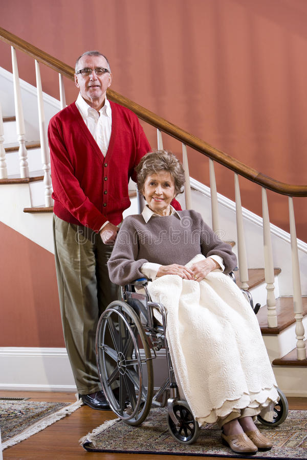 Pares sênior em casa, mulher na cadeira de rodas foto de stock