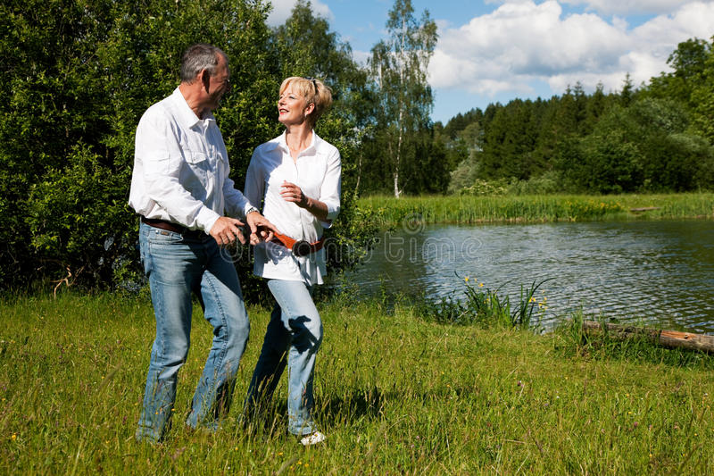 Pares sênior em um lago no verão imagens de stock