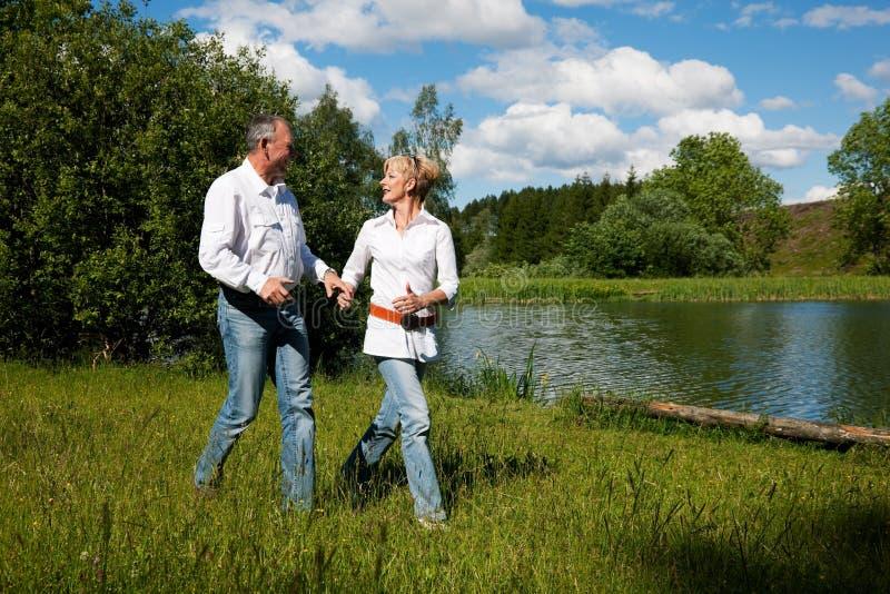 Pares sênior em um lago no verão imagem de stock royalty free