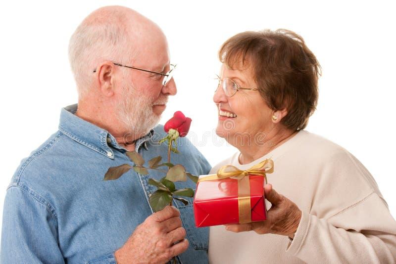 Pares sênior felizes com presente e a Rosa vermelha fotos de stock