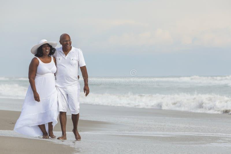 Pares sênior felizes do americano africano na praia foto de stock