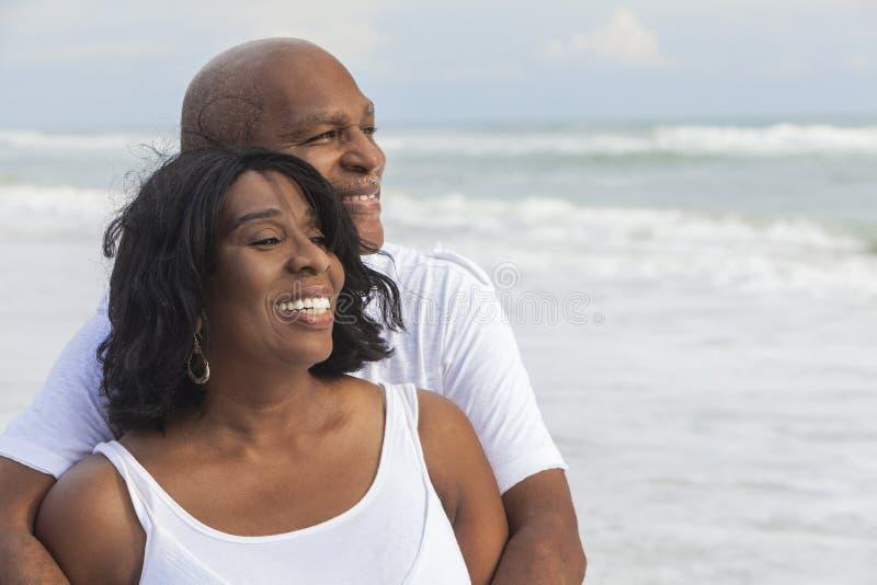 Pares sênior felizes do americano africano na praia imagem de stock royalty free