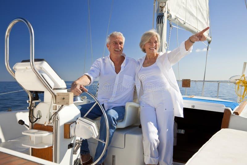 Pares sênior felizes na roda de um barco de vela imagem de stock