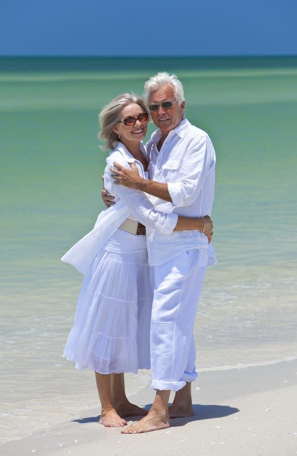 Pares sênior felizes que abraçam em uma praia tropical imagem de stock