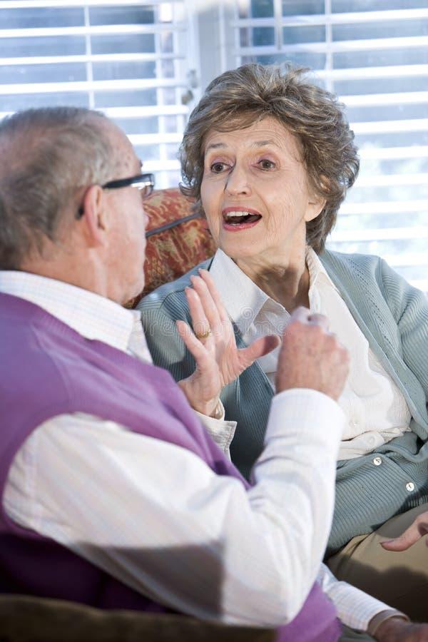 Pares sênior felizes que conversam junto no sofá imagens de stock royalty free