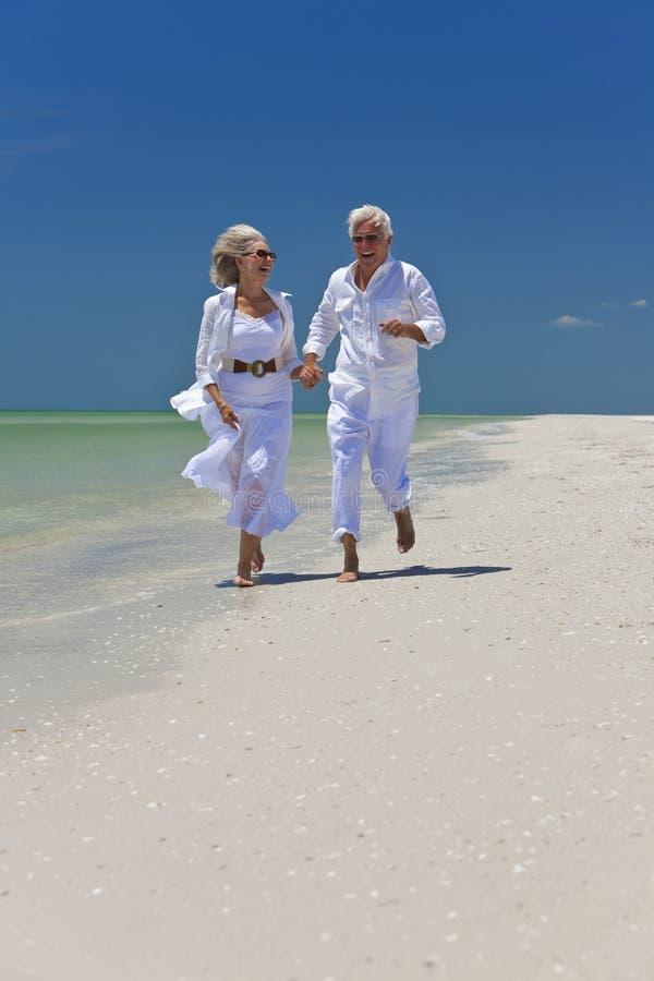 Pares sênior felizes que funcionam em uma praia tropical