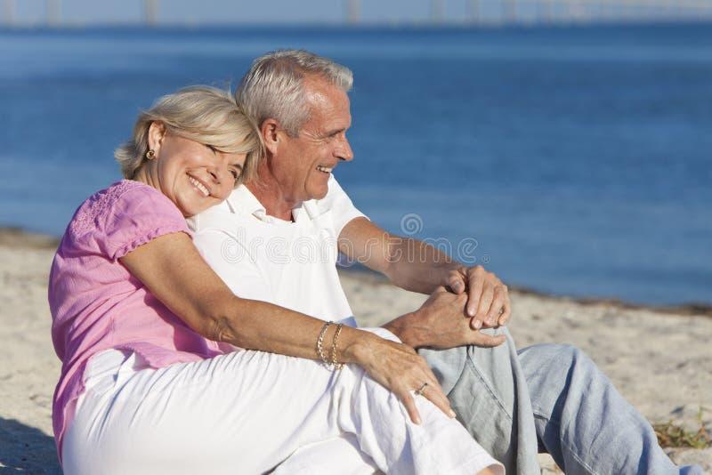 Pares sênior felizes que sentam-se junto na praia imagens de stock royalty free