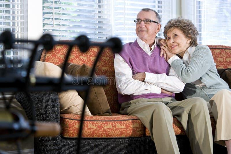 Pares sênior felizes que sentam-se junto no sofá imagem de stock royalty free