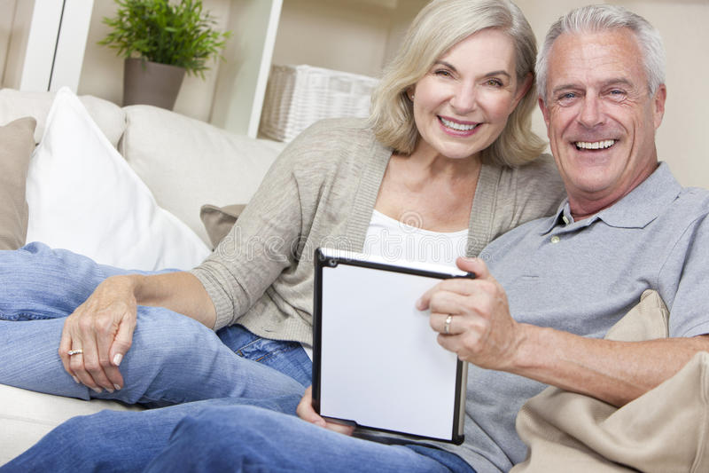 Pares sênior felizes usando o computador da tabuleta fotografia de stock royalty free
