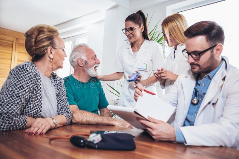 Pares sênior na discussão com o visitante da saúde em imagem de stock royalty free