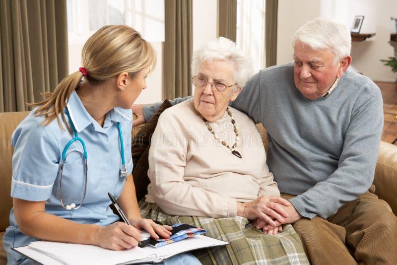 Pares sênior na discussão com o visitante da saúde em imagem de stock