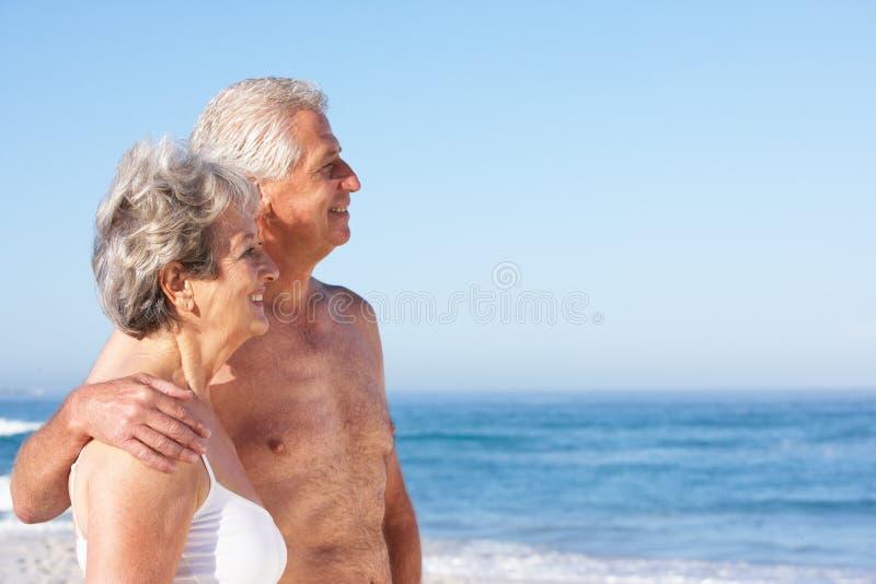 Pares sênior no feriado que anda ao longo da praia de Sandy fotografia de stock