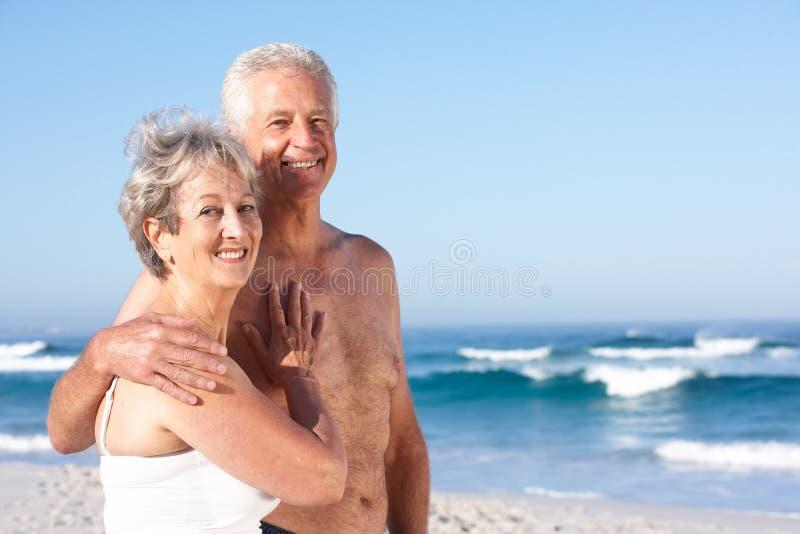 Pares sênior no feriado que anda ao longo da praia de Sandy imagem de stock