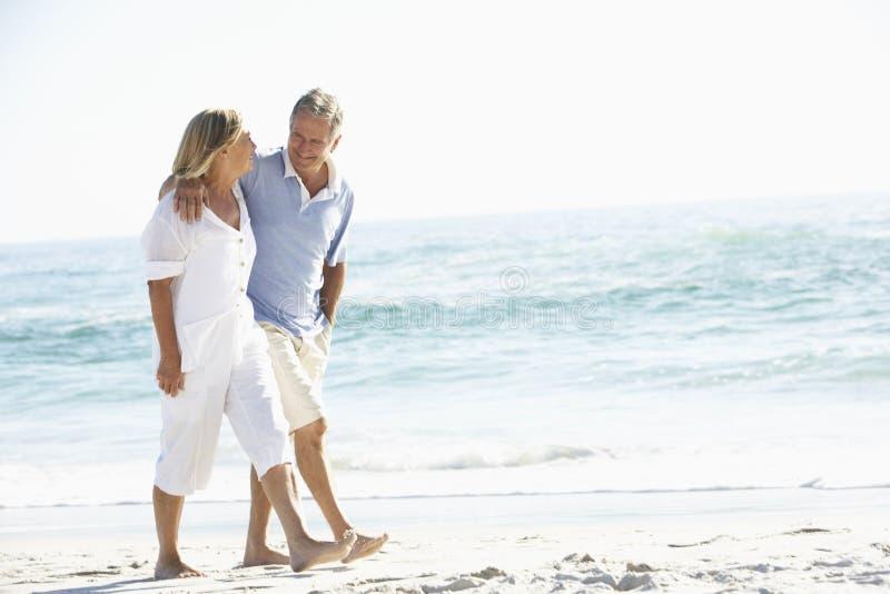 Pares sênior no feriado que anda ao longo da praia de Sandy imagens de stock royalty free