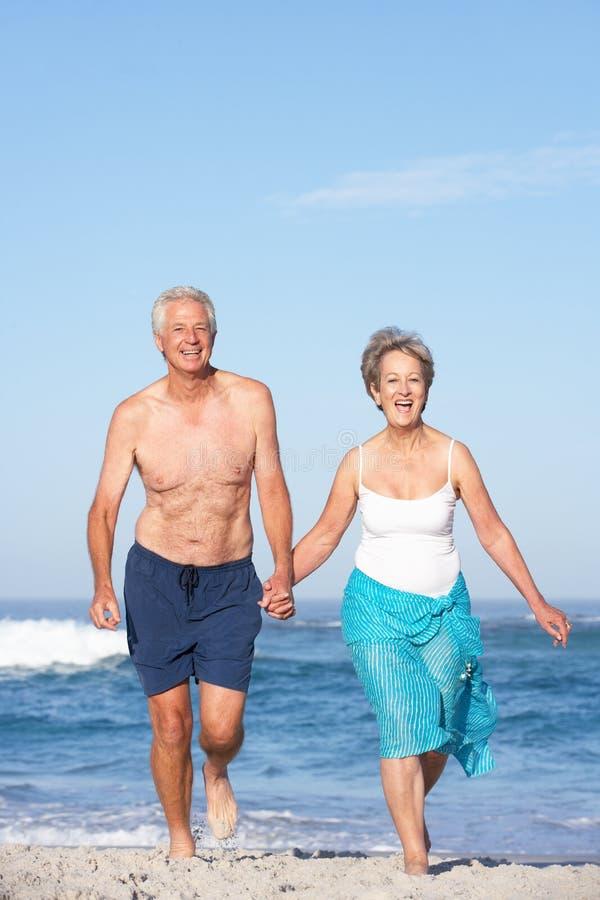 Pares sênior no feriado que funciona ao longo da praia de Sandy fotografia de stock royalty free