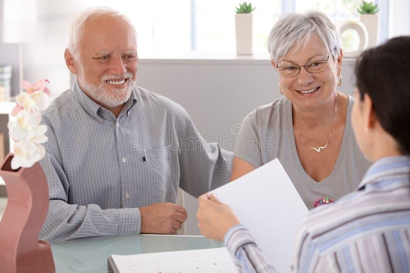 Pares sênior no sorriso financeiro do conselheiro imagens de stock