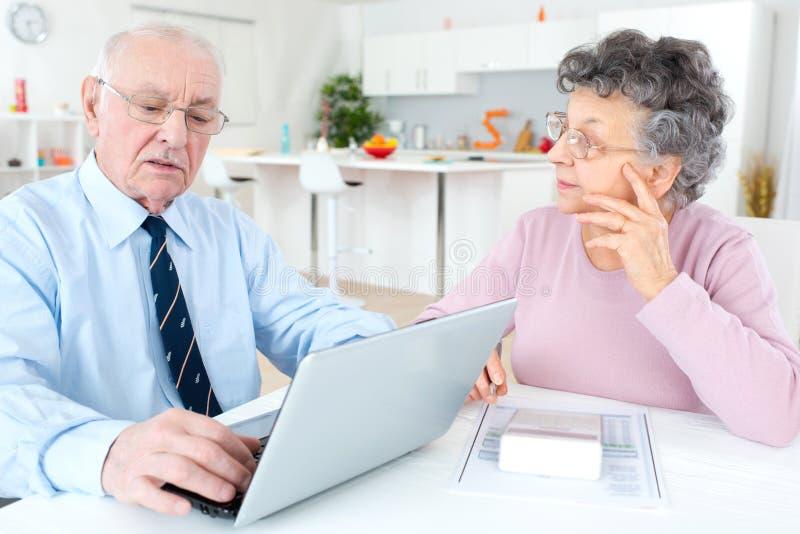 Pares sênior preocupados usando o portátil em casa fotos de stock royalty free