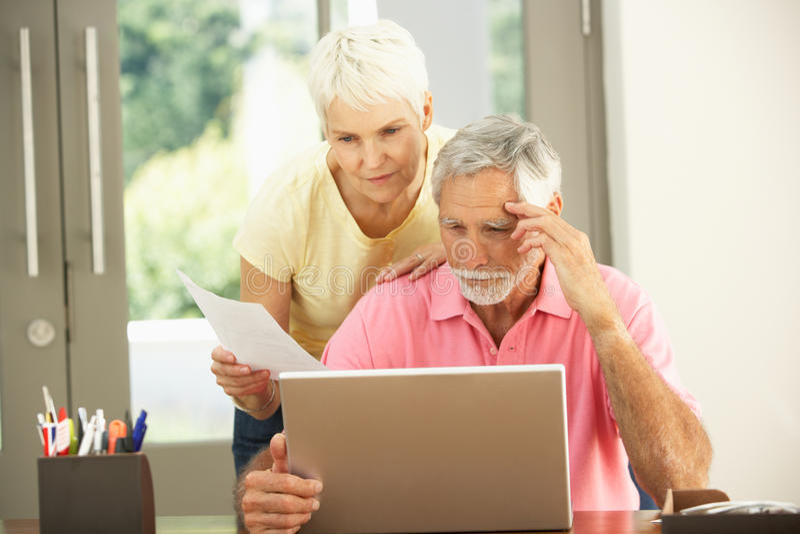 Pares sênior preocupados usando o portátil em casa imagens de stock