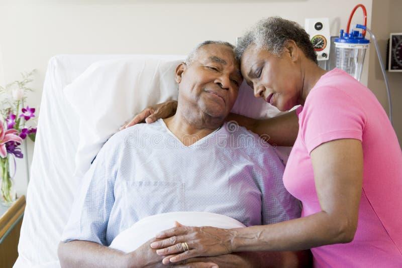 Pares sênior que abraçam no hospital foto de stock