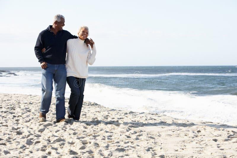 Pares sênior que andam ao longo da praia junto fotografia de stock royalty free