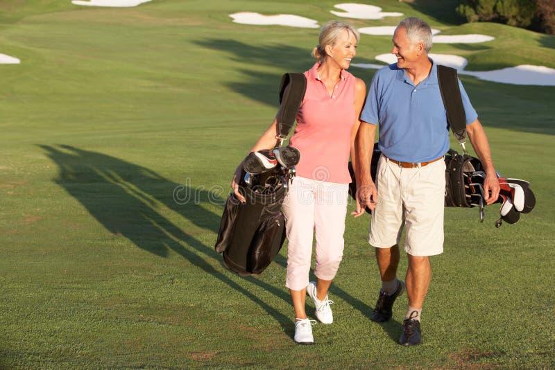 Pares sênior que andam ao longo do campo de golfe foto de stock