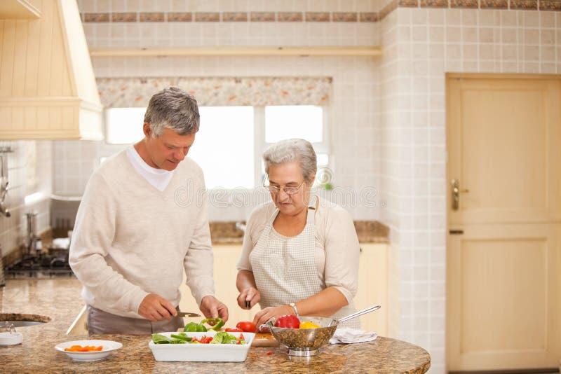 Pares sênior que cozinham na cozinha imagens de stock