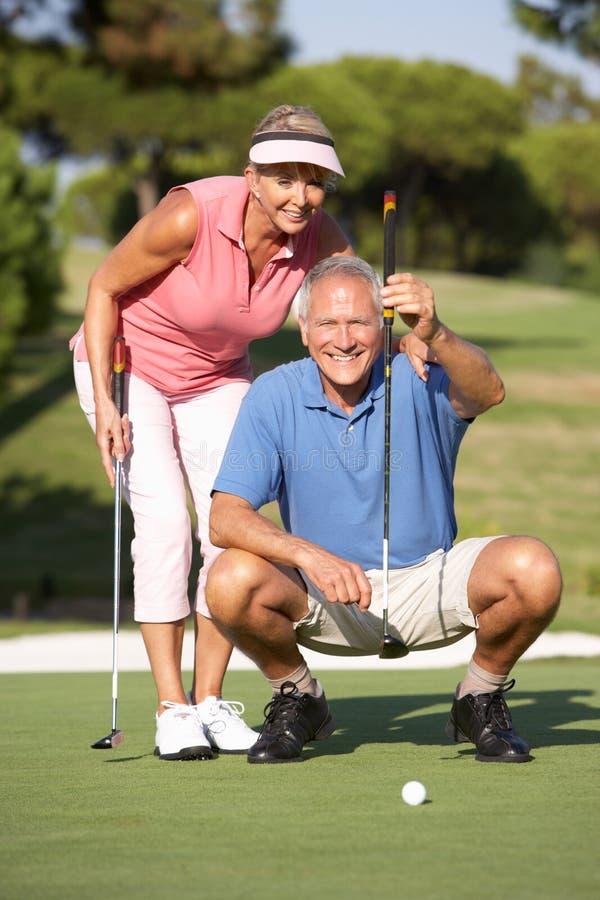 Pares sênior que Golfing no campo de golfe fotos de stock royalty free