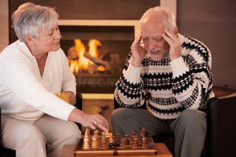 Pares sênior que jogam a xadrez em casa fotografia de stock royalty free