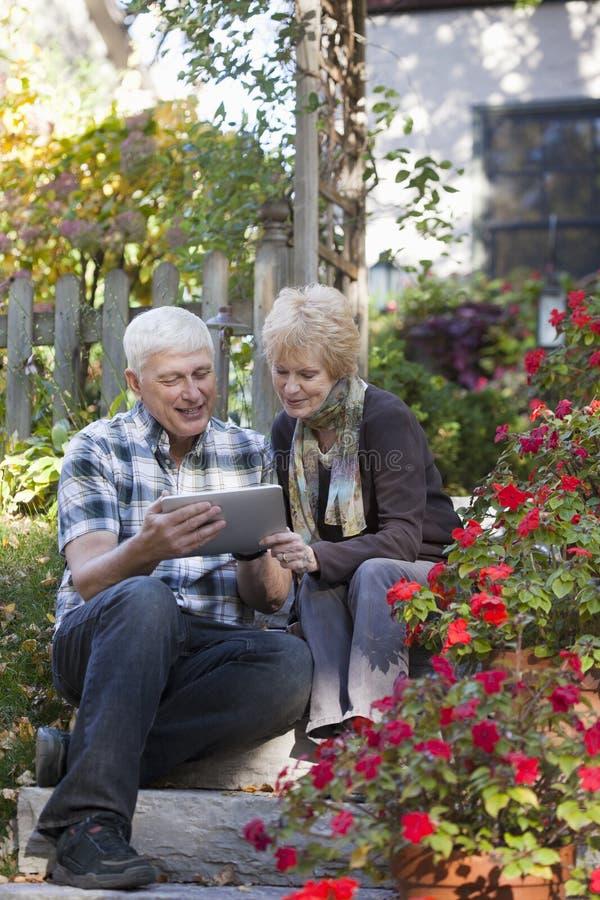 Pares sênior que olham a tabuleta digital foto de stock royalty free