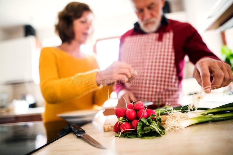 Pares sênior que preparam o alimento na cozinha imagens de stock