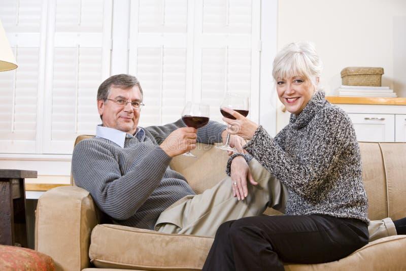 Pares sênior que relaxam junto no sofá com vinho imagens de stock royalty free