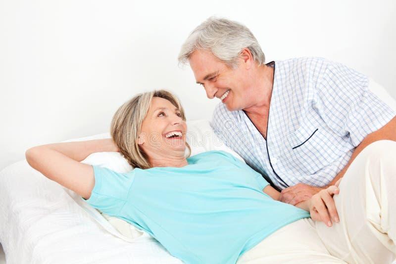 Pares sênior que riem na cama fotografia de stock