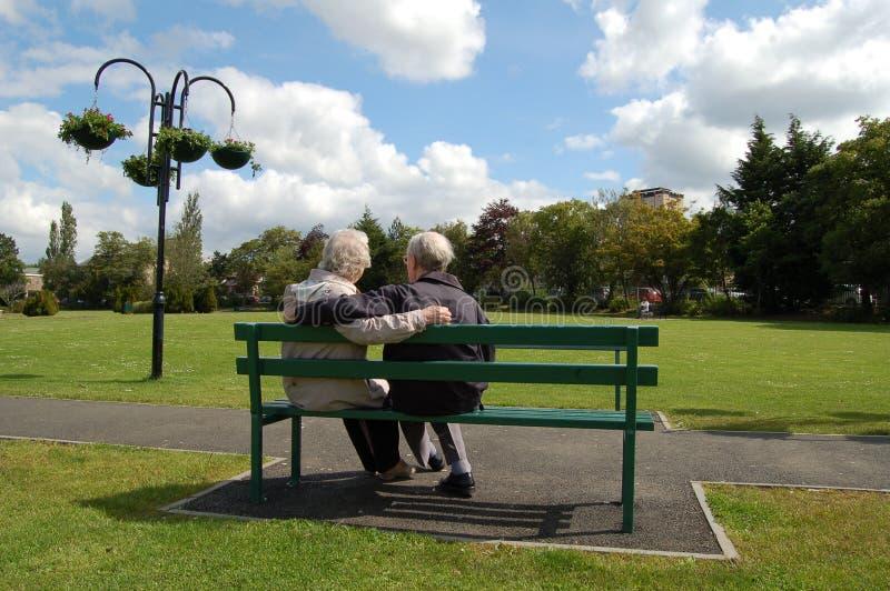 Pares sênior que sentam-se em um banco de parque fotos de stock royalty free