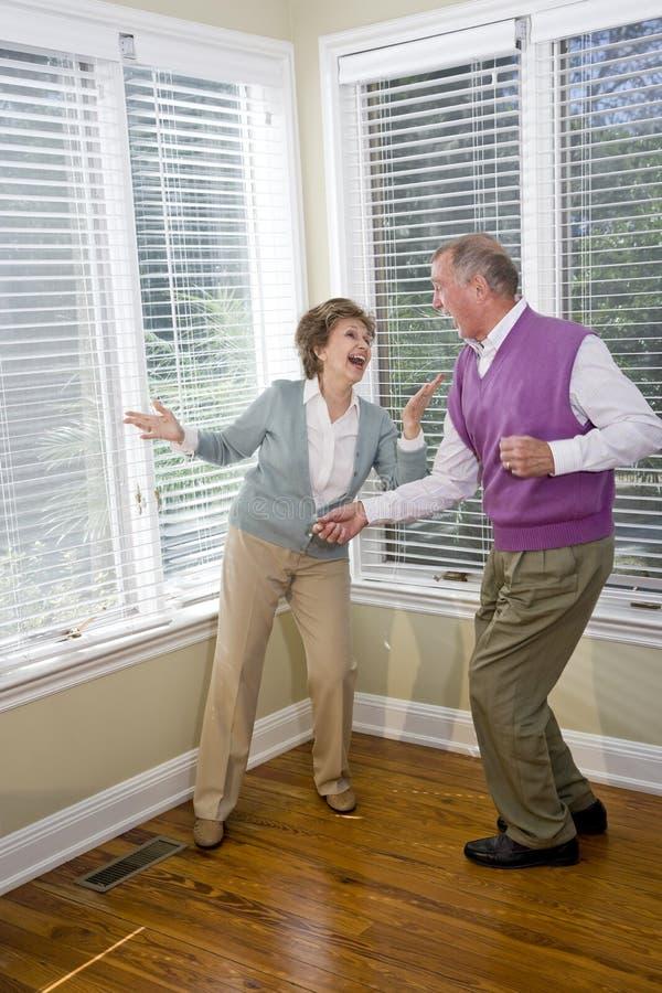 Pares sênior que têm a dança do divertimento na sala de visitas foto de stock royalty free