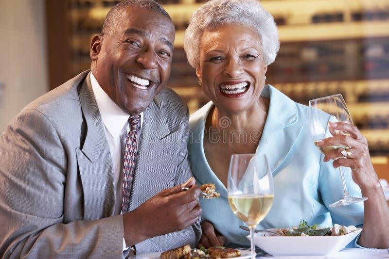 Pares sênior que têm o jantar em um restaurante imagem de stock