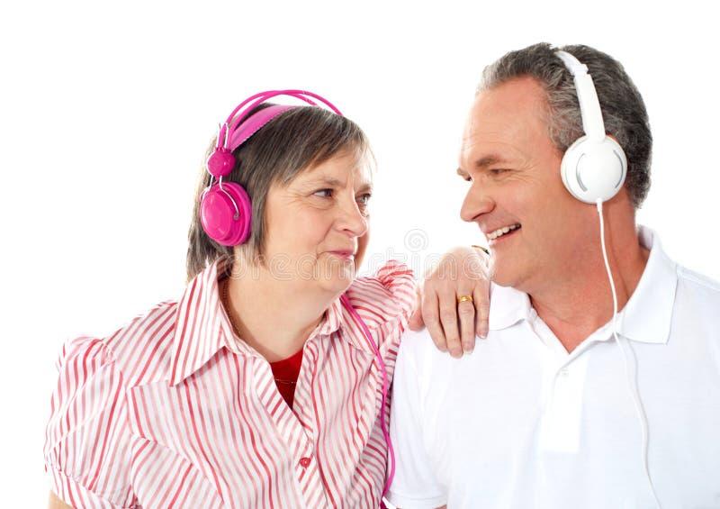 Pares sênior românticos que apreciam a música junto fotografia de stock