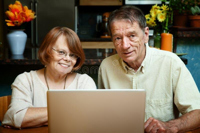 Pares sênior usando o computador portátil em casa fotos de stock royalty free