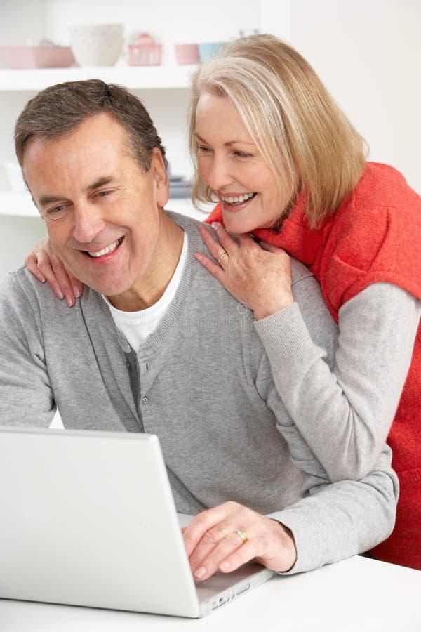 Pares sênior usando o portátil em casa imagem de stock