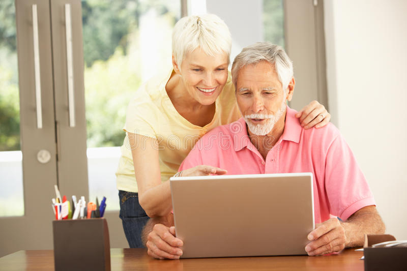 Pares sênior usando o portátil em casa fotografia de stock royalty free