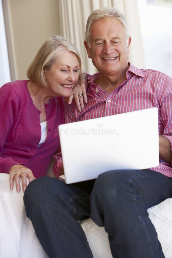 Pares sênior usando o portátil em casa fotos de stock royalty free